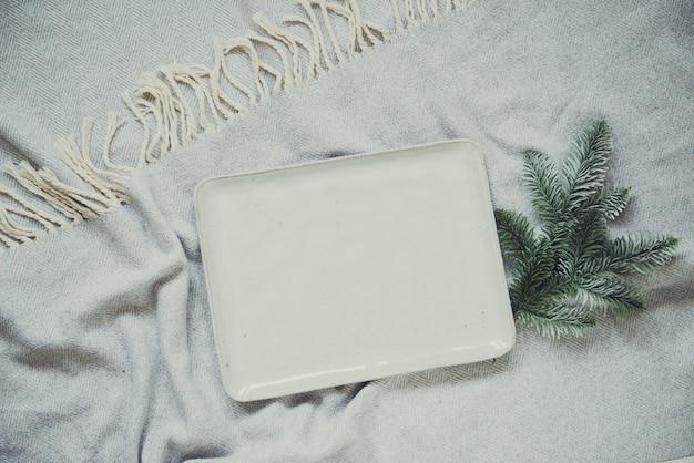Flache überkopf-weihnachtskomposition mit serviertablett auf schwarzem hintergrund mit tannenbaumbrunchdekor auf grauem gemütlichem plaid