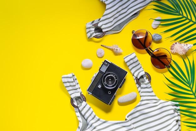 Flache überlagerung von vintage-stil strandzubehör auf trendigen gelben hintergrund. sommerurlaub.