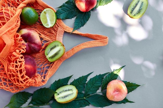Flache umweltfreundliche mesh-einkaufstasche mit früchten pfirsich, kiwi, limette auf grauer oberfläche im sonnenlicht, sommerzeit. lebensmittelkonzept, kopienraum, draufsicht.