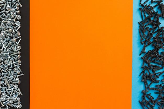 Flache verlegung mit verschiedenen schrauben auf schwarzem, orangefarbenem und blauem hintergrund. draufsicht auf das checklistenkonzept
