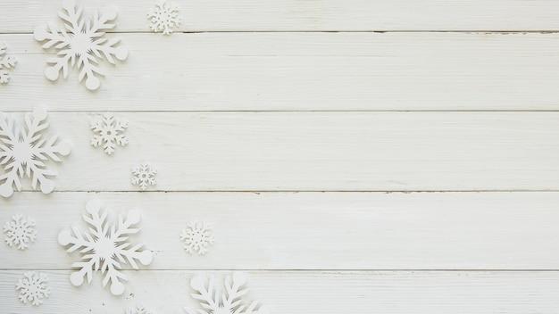 Flache weihnachtsdekorationsschneeflocken auf holzbrett legen