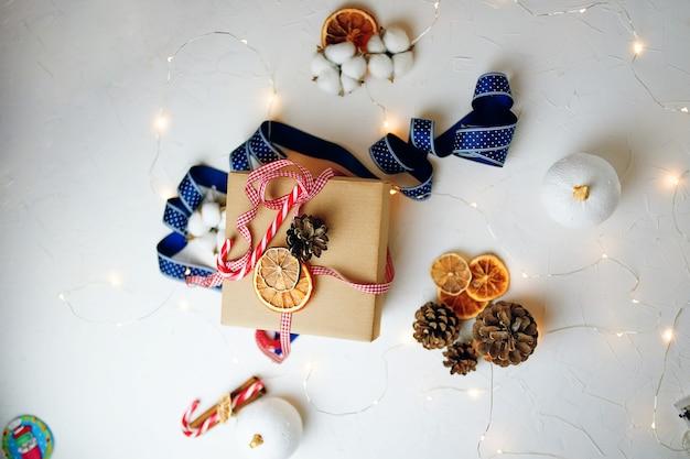 Flache weihnachtsgeschenkbox und dekorationen auf weißem strukturiertem tisch neue jahre atmosphäre süßigkeiten ca...