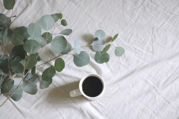 Flache weiße keramikbecher mit kaffee neben silberdollar-kaugummibaumblättern auf weißem bettlaken