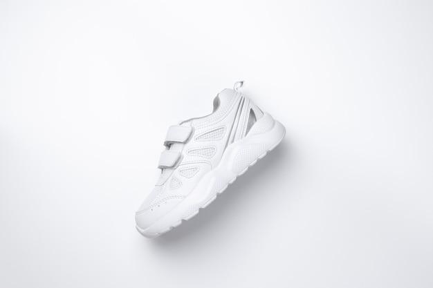 Flache weiße kinder-sneaker mit seitlichen klettverschlüssen mit weichen schatten in der mitte... Premium Fotos