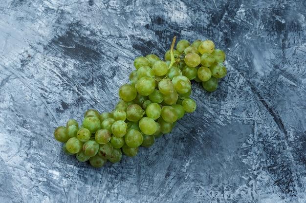 Flache weiße trauben auf dunkelblauem marmorhintergrund legen. horizontal