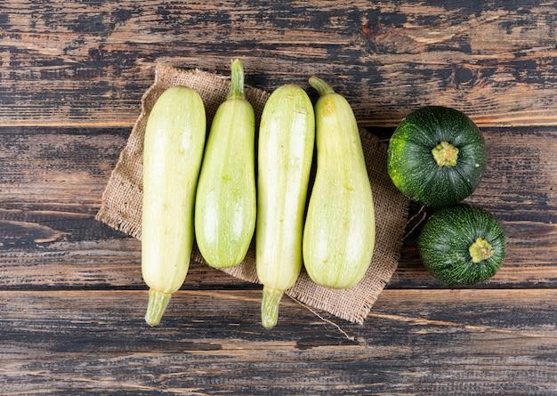 Flache weiße und grüne zucchini auf dunklem holztisch