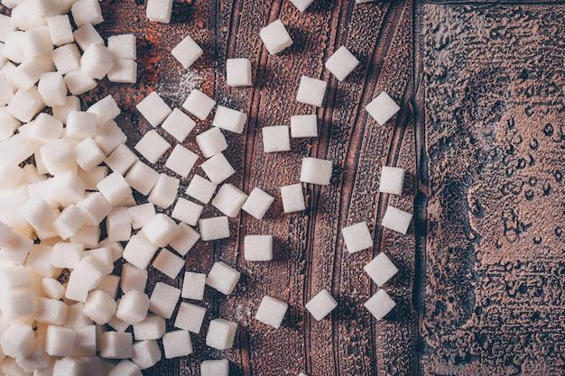Flache weiße zuckerwürfel auf dunklen holztisch legen. horizontal
