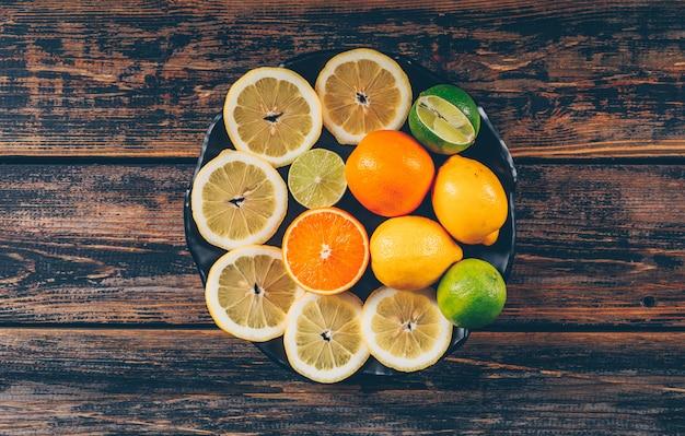 Flache zitronenscheiben in teller mit orangen und grüner zitrone auf dunklem holzhintergrund legen. horizontaler raum für text