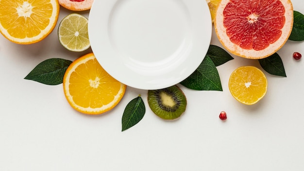 Flache zitrusfrucht mit blättern und teller