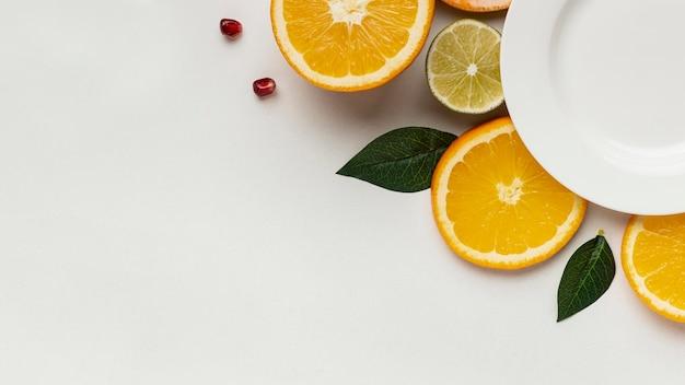 Flache zitrusfrucht mit teller und kopierraum