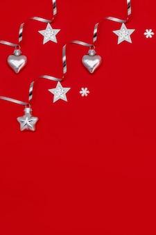 Flache zusammensetzung der weihnachtsdekorationen in silber auf rotem grund.