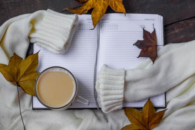 Flache zusammensetzung des herbstlaubs mit warmem pullover und tasse kaffee.