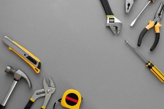 Flache zusammensetzung mit bau- und reparaturwerkzeugen auf grauem hintergrund, platz für text