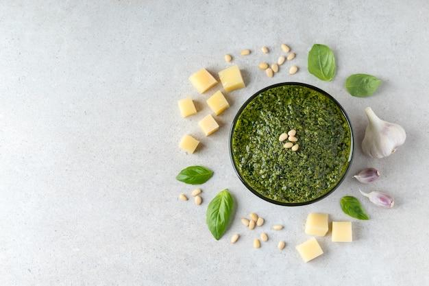 Flache zusammensetzung mit gesunder grüner pestosauce und zutaten auf grauem tisch