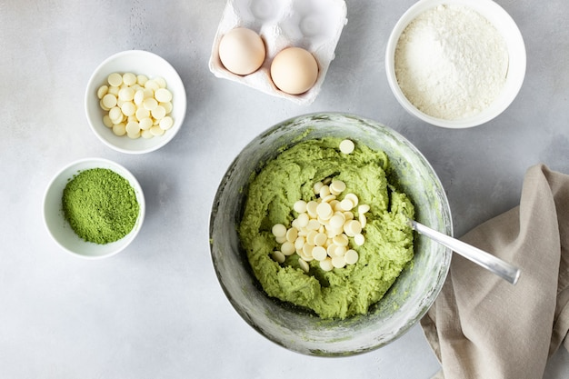 Flache zusammensetzung mit grünem tee matcha teig, weißen schokoladenstückchen