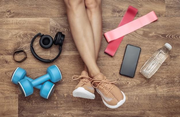 Flache zusammensetzung von frauenbeinen, sportgeräten und kleidung auf einem holzboden. fitness-, sport- und gesundes lifestyle-konzept. ansicht von oben