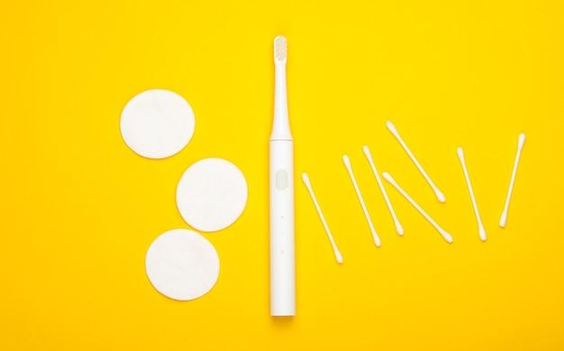 Flache zusammensetzung von hygieneprodukten. zahnbürste, wattepads, ohrstöpsel auf gelbem grund. draufsicht