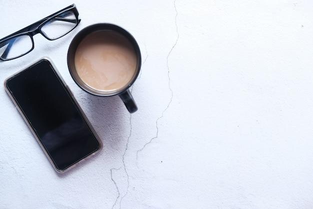 Flache zusammensetzung von smartphone und kaffee auf dem tisch