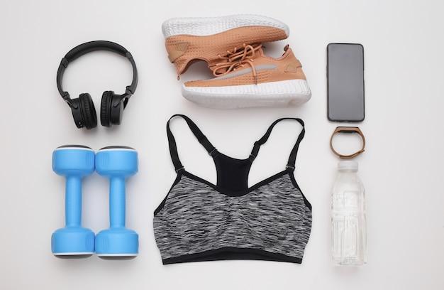 Flache zusammensetzung von sportgeräten, kleidung auf weißem hintergrund. fitness-, sport- und gesundes lifestyle-konzept. ansicht von oben