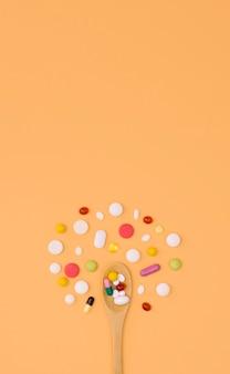 Flache zusammenstellung von pillen mit löffel und kopierraum