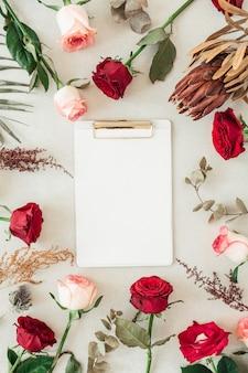 Flache zwischenablage mit leerem kopierraum für text im rahmenrand von rosa, roten rosenblüten, protea, tropischem palmblatt, eukalyptus auf beige