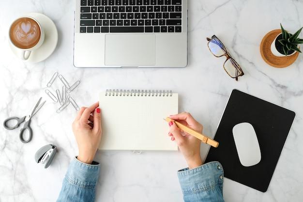 Flacher arbeitsbereich. frauenhand mit kaffeetasse, smartphone, computer, notizbuch, planer und stationär mit kopie spacetop ansicht.