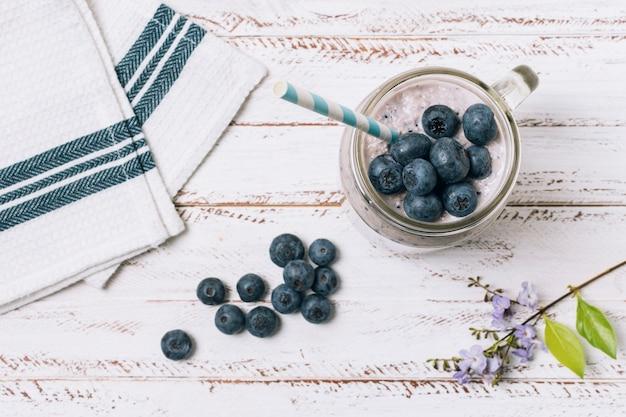 Flacher blaubeer-smoothie neben handtuch