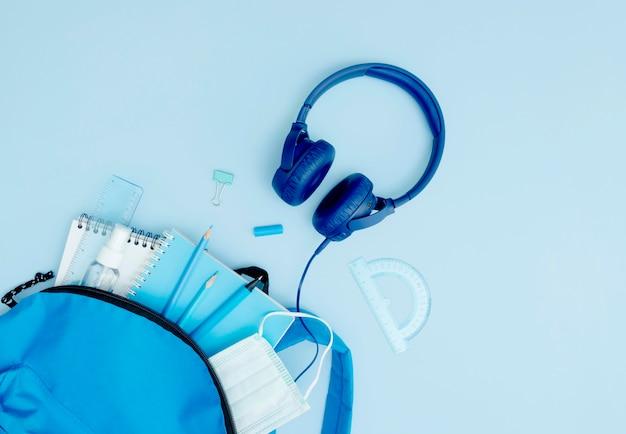 Flacher blauer rucksack mit schulmaterial