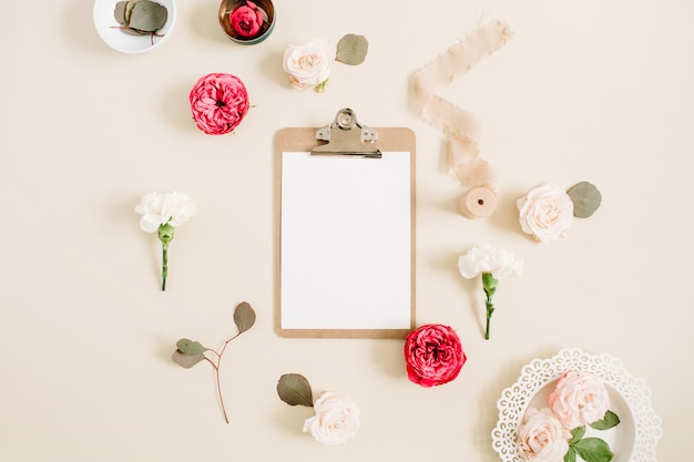 Flacher blumenrahmen mit leerem klemmbrett, roten und beigen rosenblütenknospen, weißer nelke, eukalyptus, band auf hellbeigem pastell