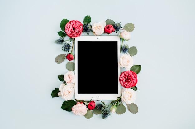 Flacher blumenrahmen mit tablette, roten und beige rosenblütenknospen auf blassem pastellblauem hintergrund. ansicht von oben