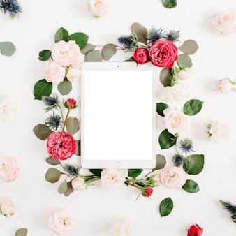 Flacher blumenrahmen mit tablette, roten und beige rosenblütenknospen auf weißem hintergrund. ansicht von oben