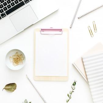 Flacher büroarbeitsplatz mit leerer zwischenablage, laptop und briefpapier auf weißem hintergrund