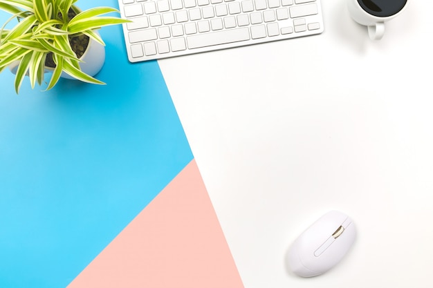 Flacher büroschreibtisch des modernen arbeitsplatzes mit laptop auf blauem rosa und weißem tisch,