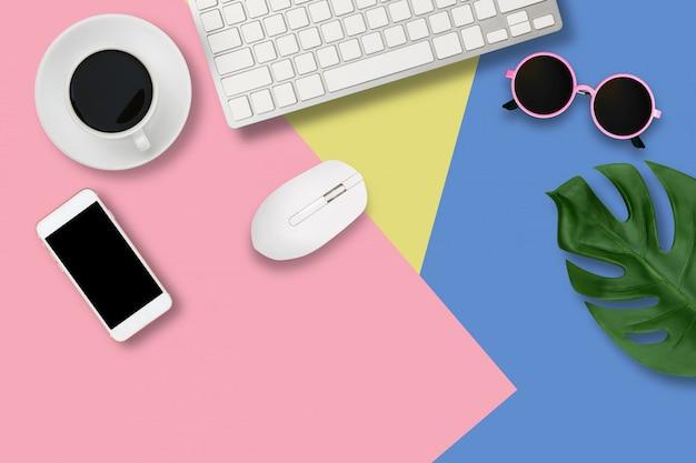 Flacher büroschreibtisch des modernen arbeitsplatzes mit laptop auf blauem und rosa tisch,