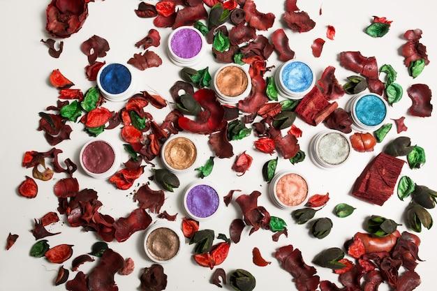 Flacher cremefarbener lidschatten und glitzer mit trockenblumen auf weißem hintergrund