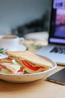 Flacher dof des vegetarischen sandwiches mit laptop und kaffee auf unscharfem rücken