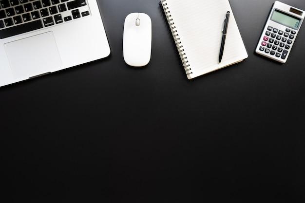 Flacher, draufsichtbürotischschreibtisch. arbeitsbereich mit taschenrechner, stift, laptop, anmerkung über den schwarzen hintergrund