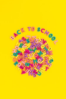 Flacher draufsichttext zurück zur schule auf gelbem hintergrund