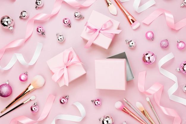 Flacher feiertagshintergrund mit weihnachtsball, geschenk, band, make-up-pinsel und dekorationen in der pastellrosa farbe. flache lage, ansicht von oben