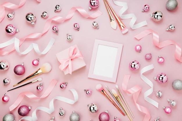 Flacher feiertagshintergrund mit weihnachtskugel, geschenk, band, make-up-pinsel und mockup-karte in pastellrosa. flache lage, ansicht von oben