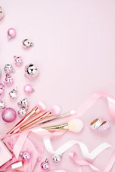 Flacher feiertagshintergrund mit weihnachtskugel, geschenk, band und dekorationen in der pastellrosafarbe. flache lage, ansicht von oben