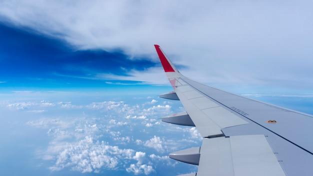 Flacher flügel auf dem blauen himmel und den wolken, kann für den luftverkehr zum reisen genutzt werden
