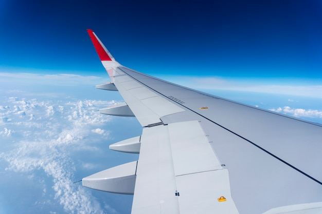 Flacher flügel auf dem blauen himmel und den wolken