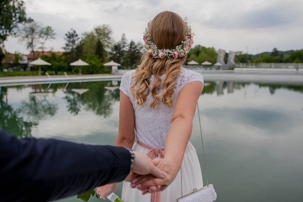 Flacher fokus der braut, die mit dem bräutigam händchen hält und zu einem pool in einem resort geht