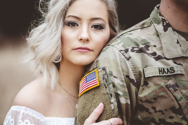 Flacher fokus einer attraktiven frau, die den arm eines amerikanischen soldaten hält
