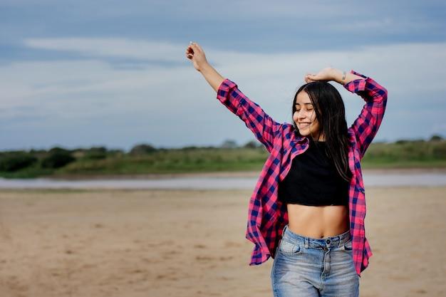 Flacher fokus einer erwachsenen fröhlichen hispanischen frau, die ein bauchfreies top mit einem flanellhemd am strand trägt