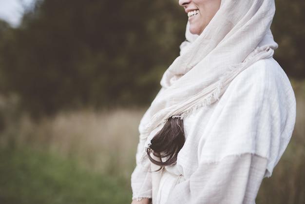 Flacher fokus einer frau, die ein biblisches gewand trägt und auf einem feld lächelt