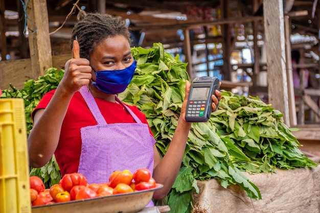 Flacher fokus einer frau mit gesichtsmaske, die einen pos-automaten auf einem markt hält holding