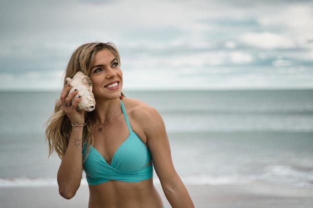 Flacher fokus einer fröhlichen, attraktiven blonden frau, die eine muschelschale hält, die dem ozean lauscht