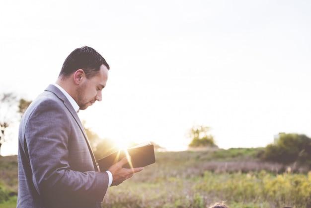 Flacher fokus einer gut gekleideten person, die die bibel liest